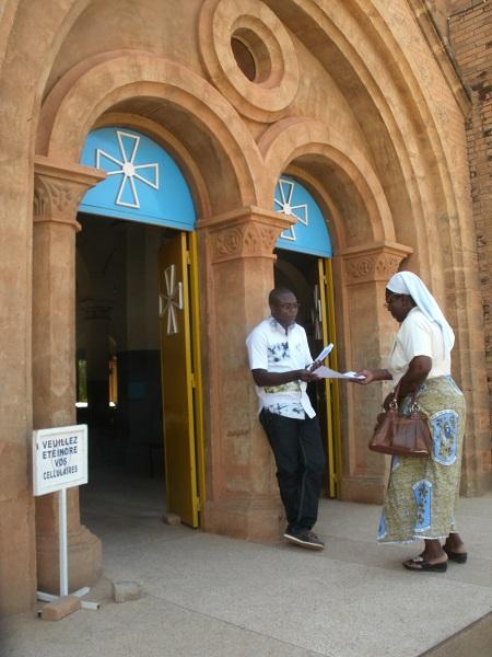 Emile accueille les religieux/ses avec les feuilles de chants